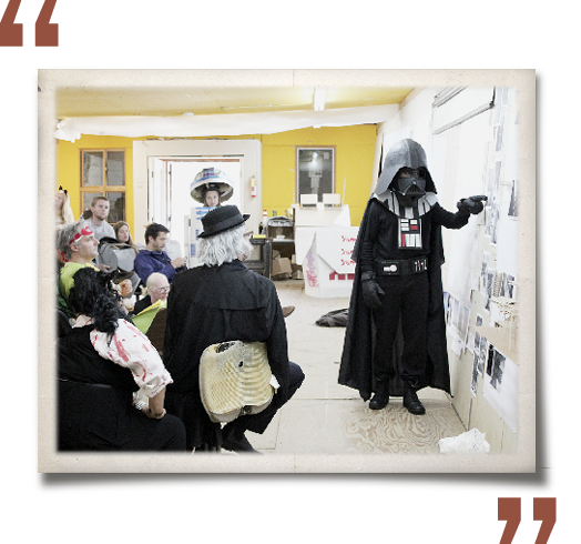 Bold rust-colored quotation marks around a photograph of Halloween Reviews in Red Barn. Darth Vader is presenting his work in front of a costumed audience