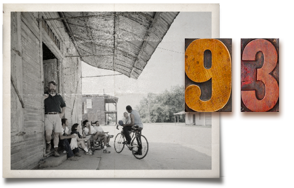 Co-founder Samuel Sambo Mockbee standing next to students on the steps of the old thesis barn in downtown Newbern. The numeral 93 made with wooden letterpress blocks overlays the photograph