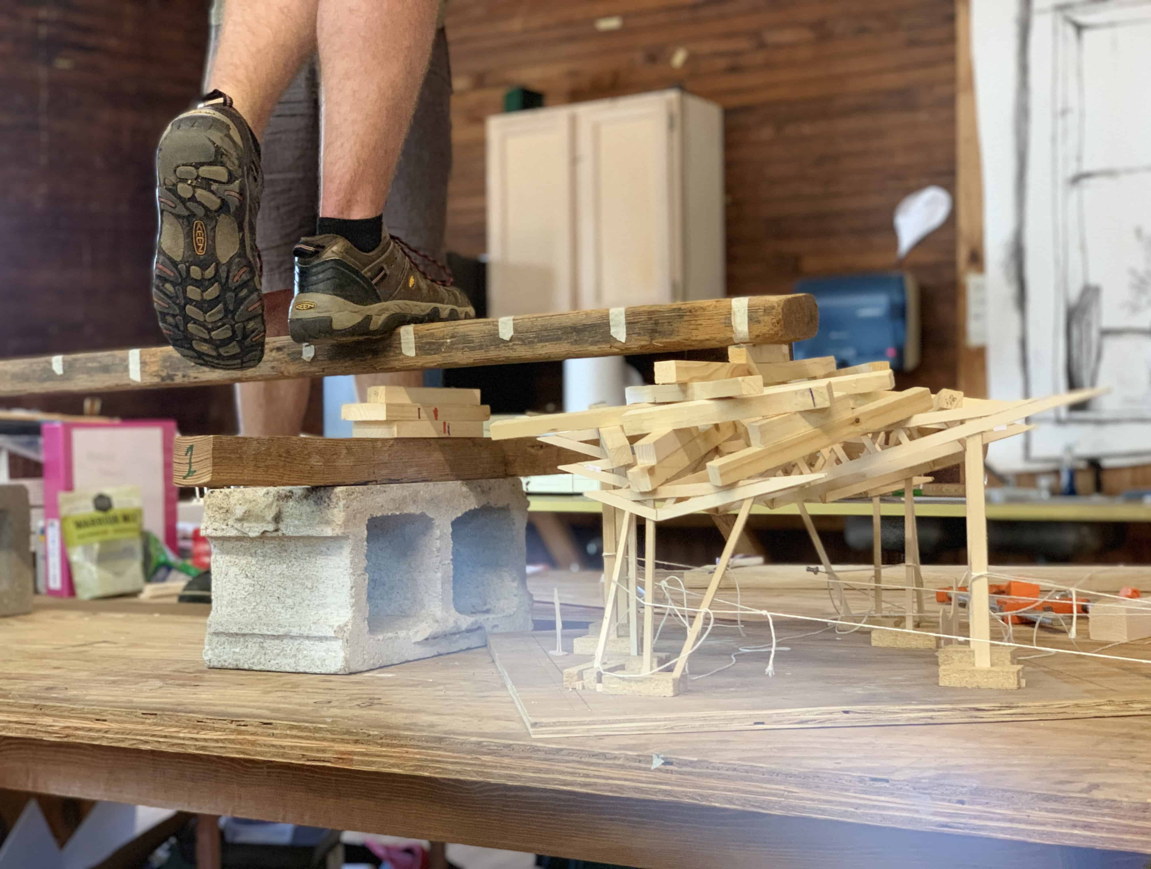 students test truss strength by standing on model