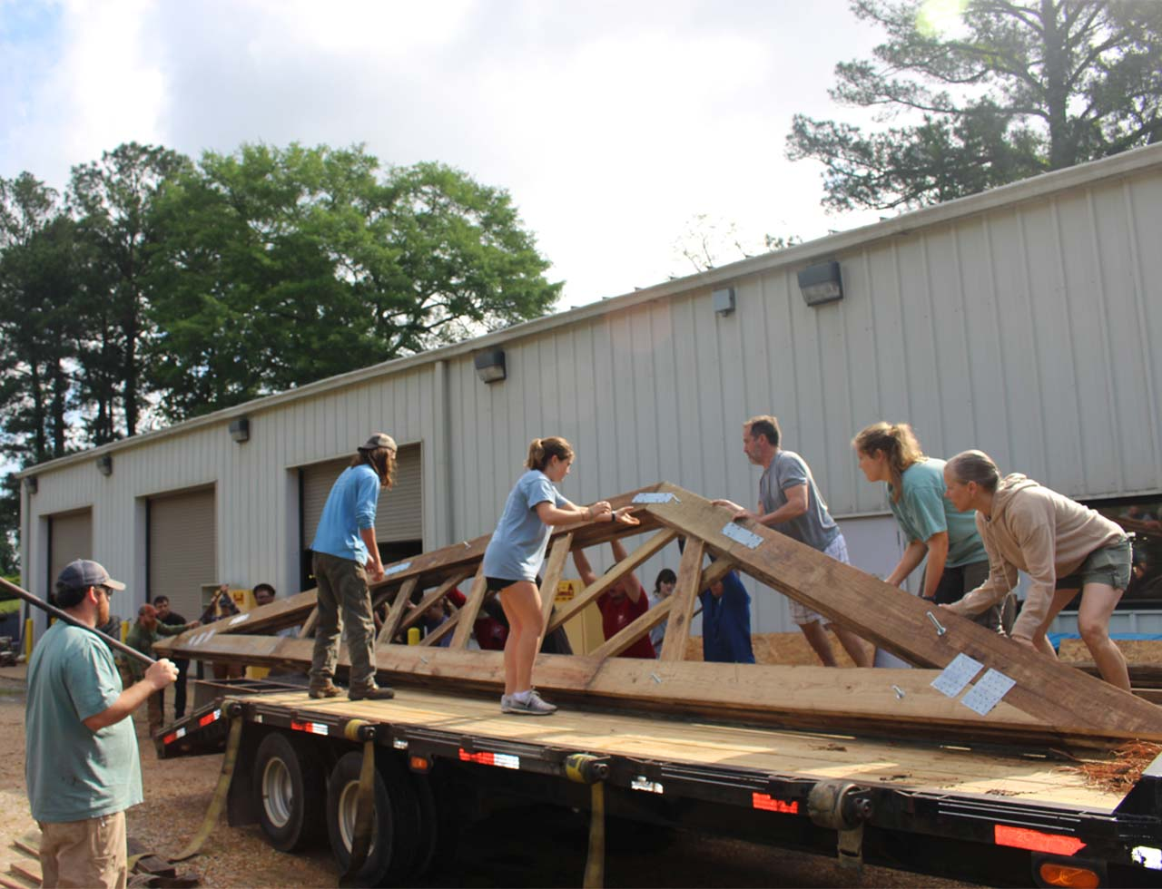 students and helpers unload trusses