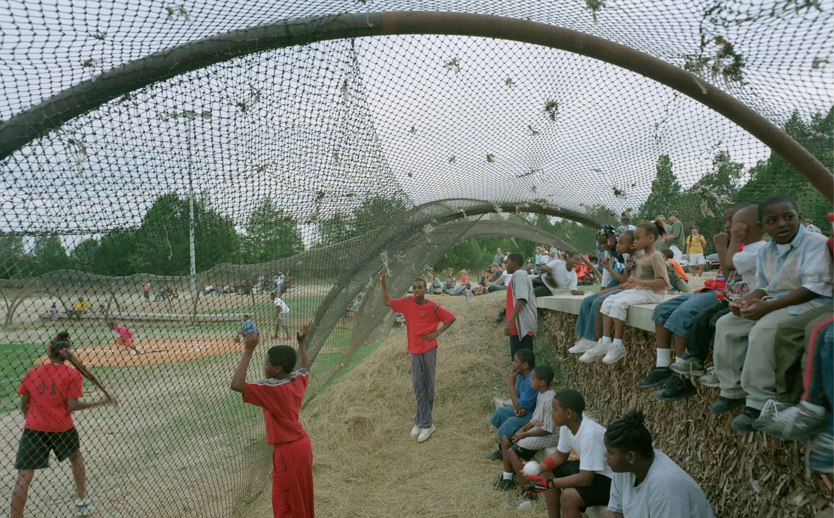 boy looking toward camera holding on to protective netting