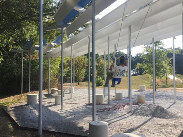 Student on a swing under the shade structure