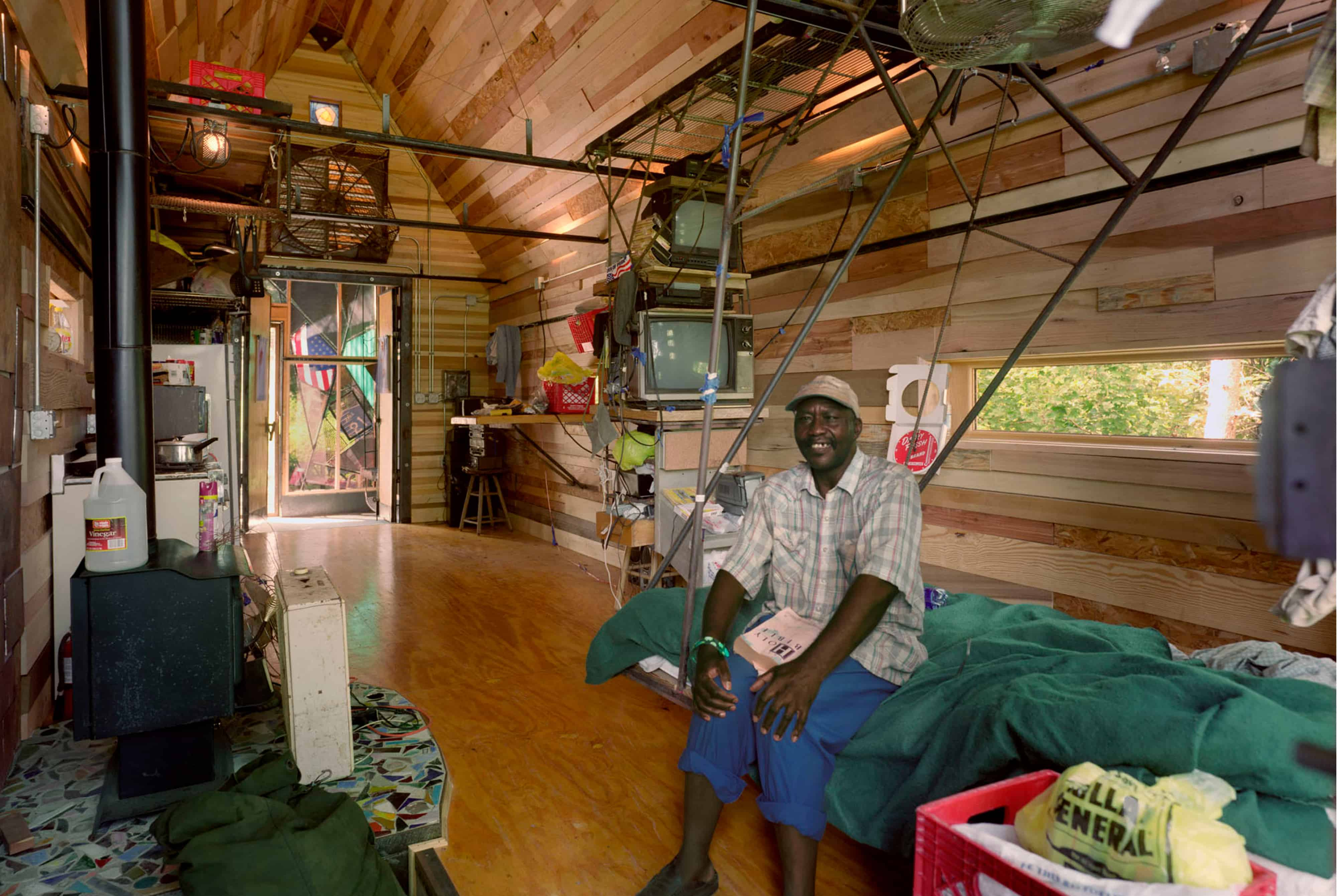 Music Man sitting inside his home surrounded by items he has collected