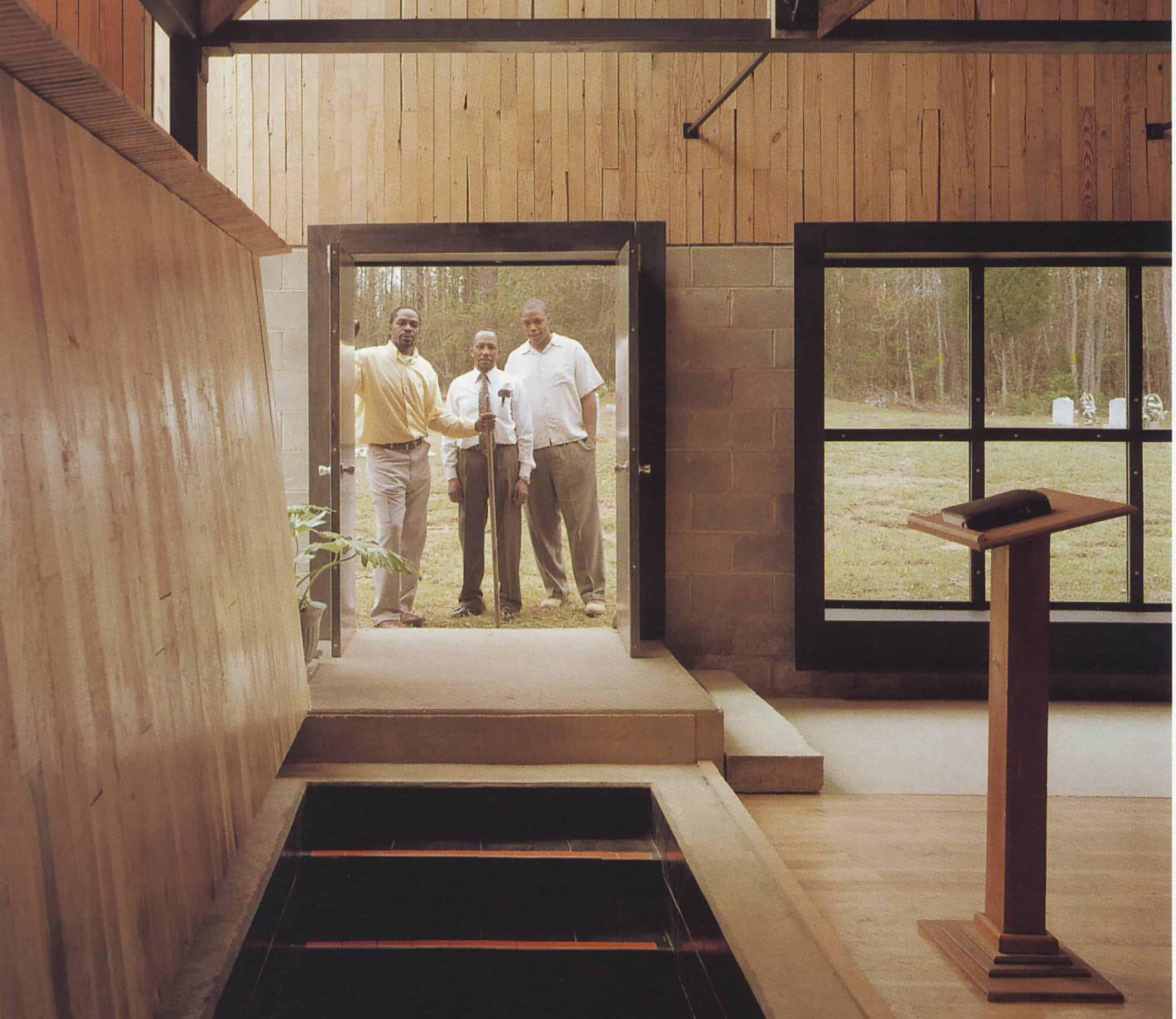 three men stand in doorway looking into church