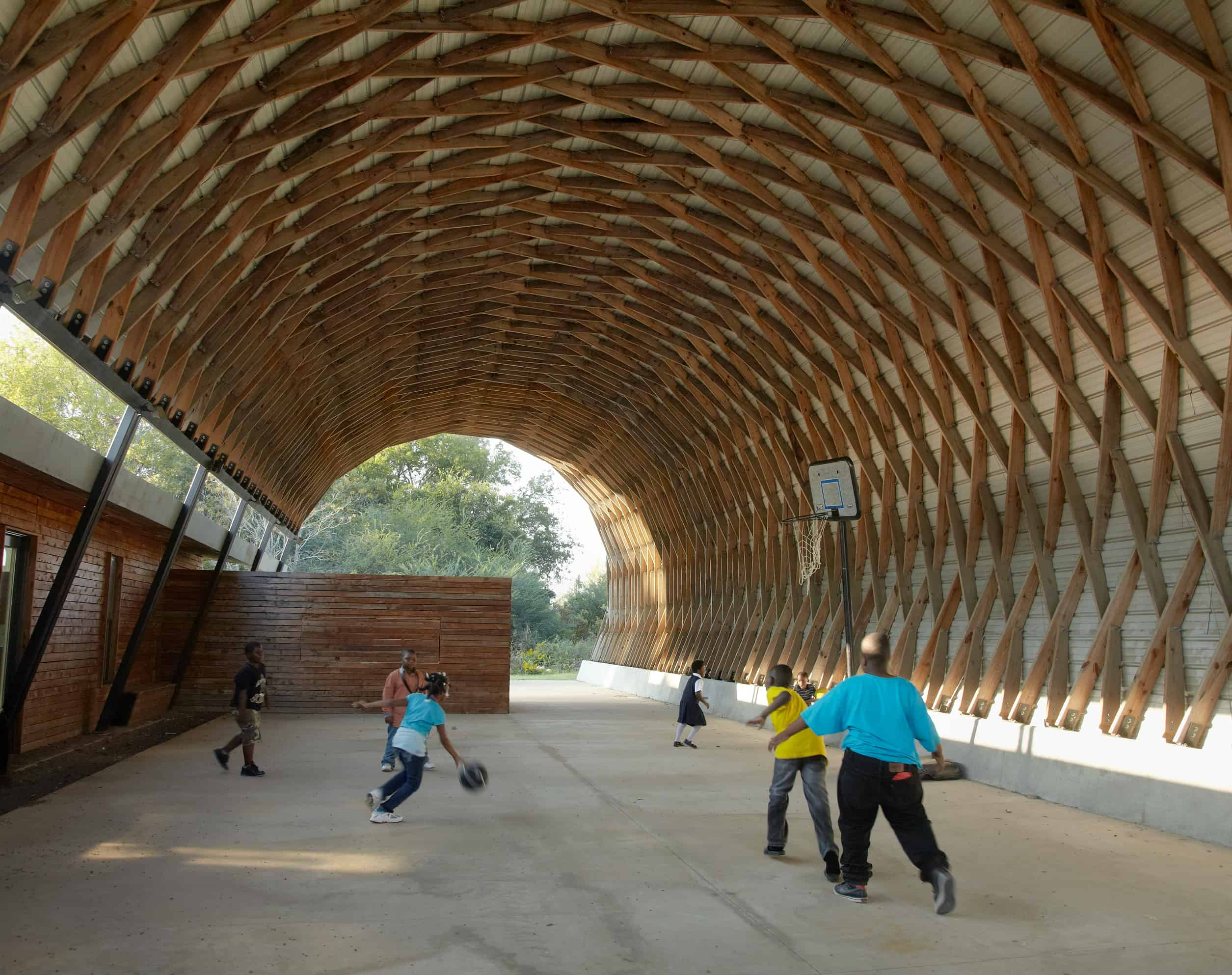 kids play basketball under the Lamella structure attached to the Club