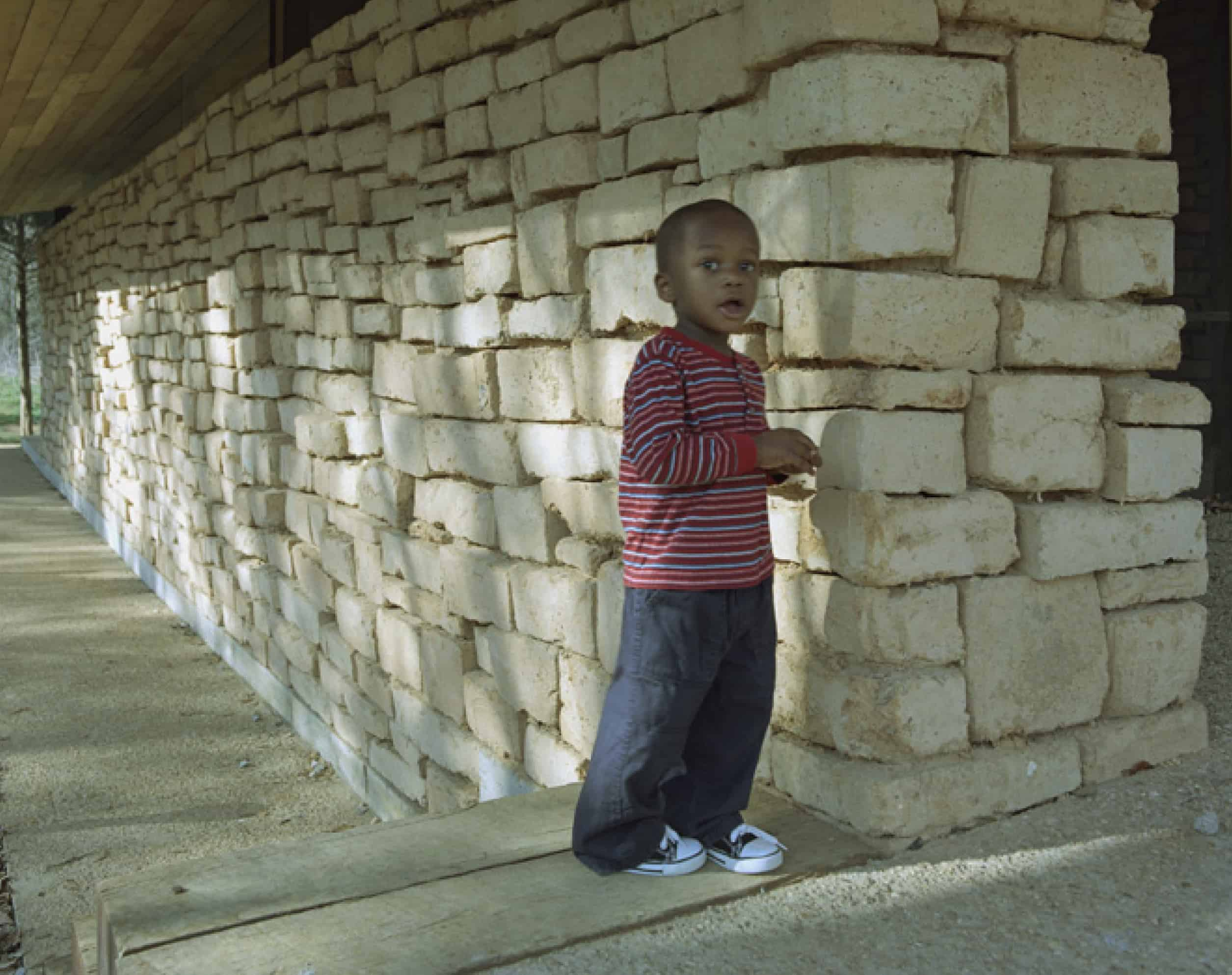 young boy stands in front of papercrete brick wall