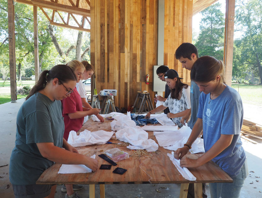 students dyeing material with indigo under pavilion