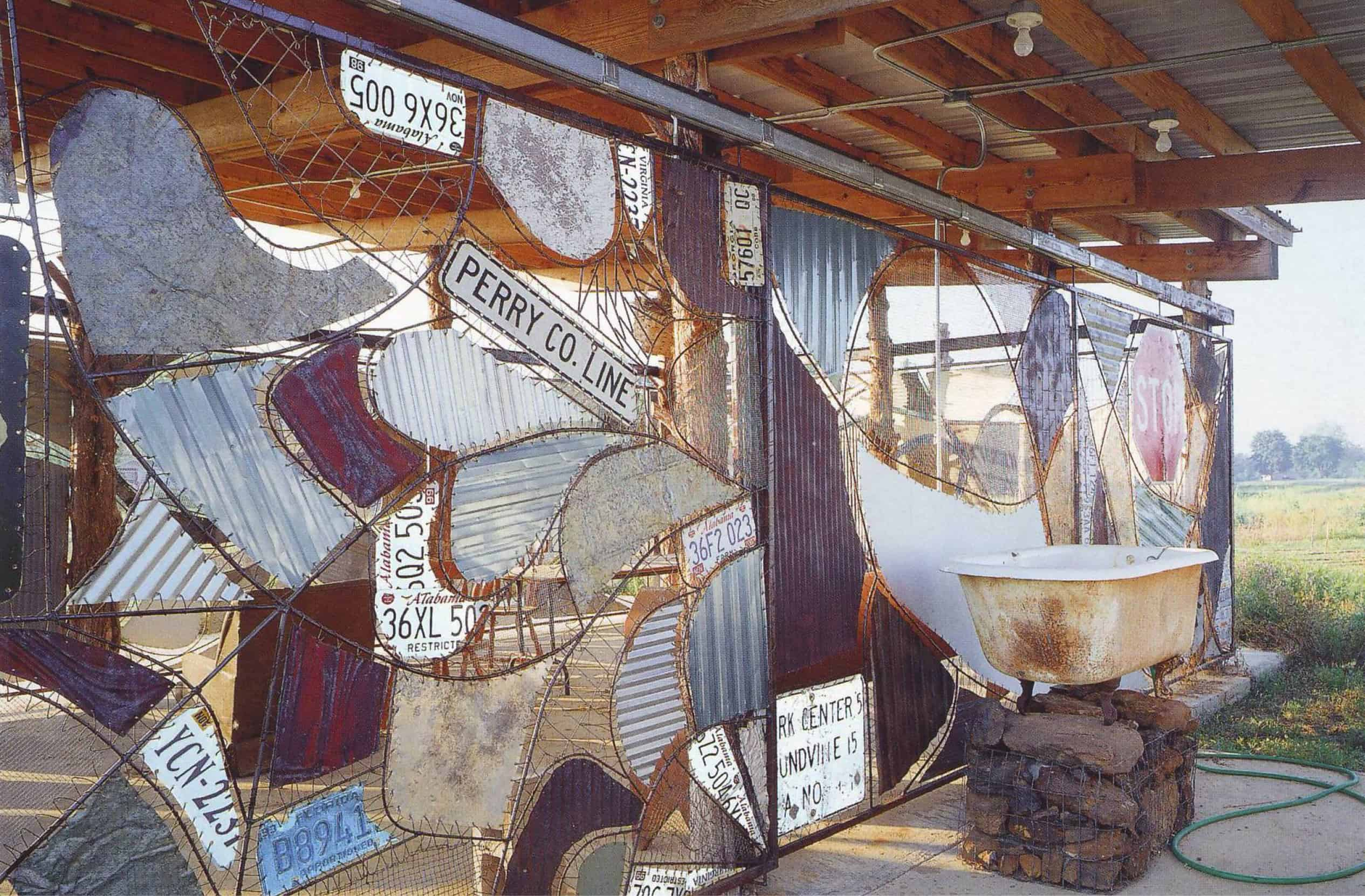 side view of stand showing wall made of scraps (license plates, road signs, corrugated metal)