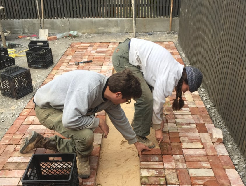 students laying brick courtyard
