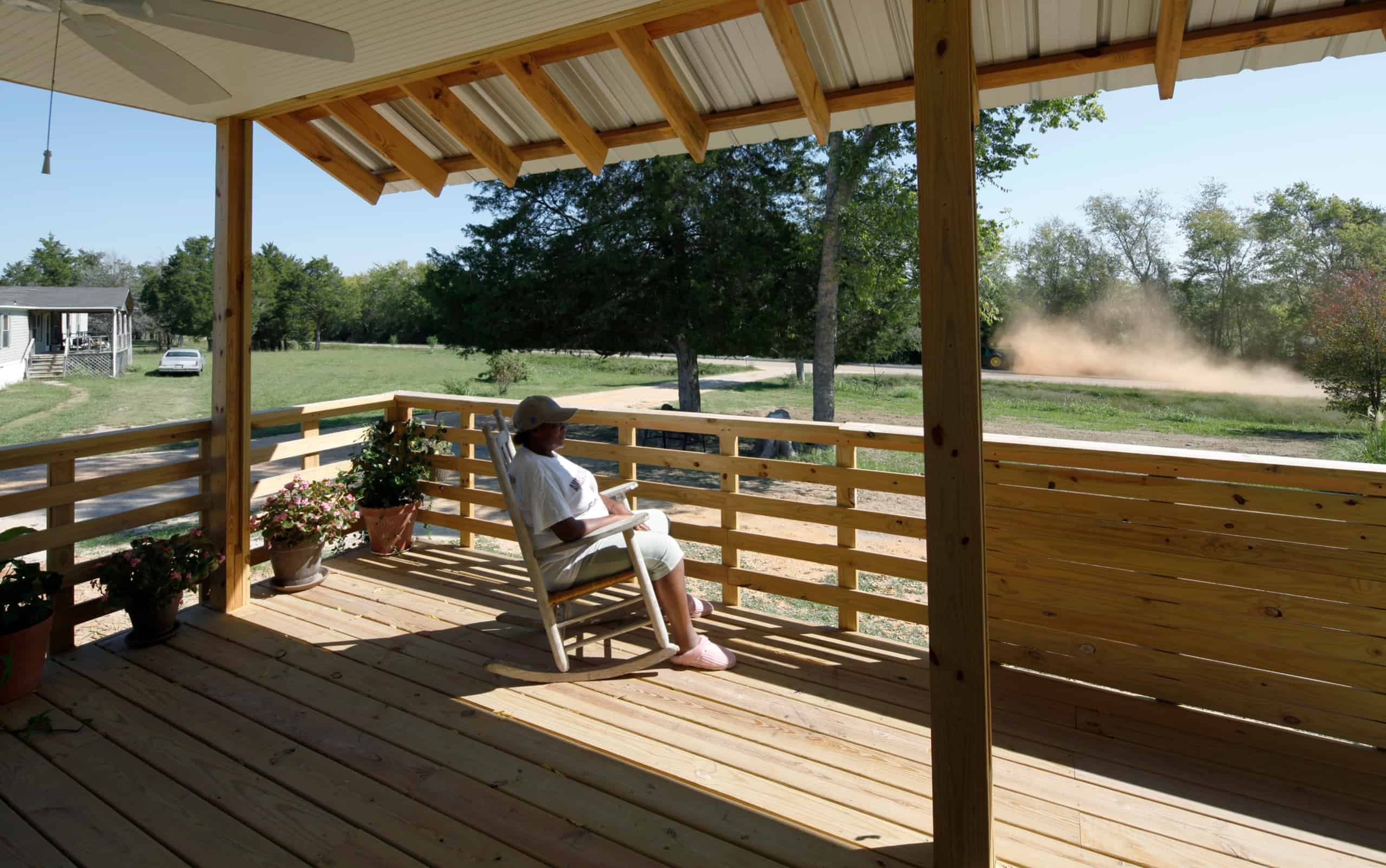 Joanne sitting on her porch in a rocking chair watching a tractor go by, stirring up dust