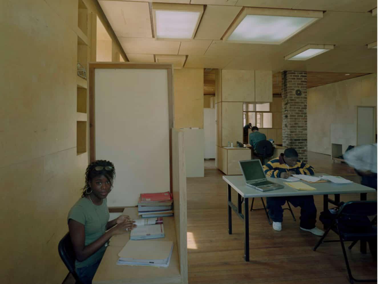 student at desk looking at the camera
