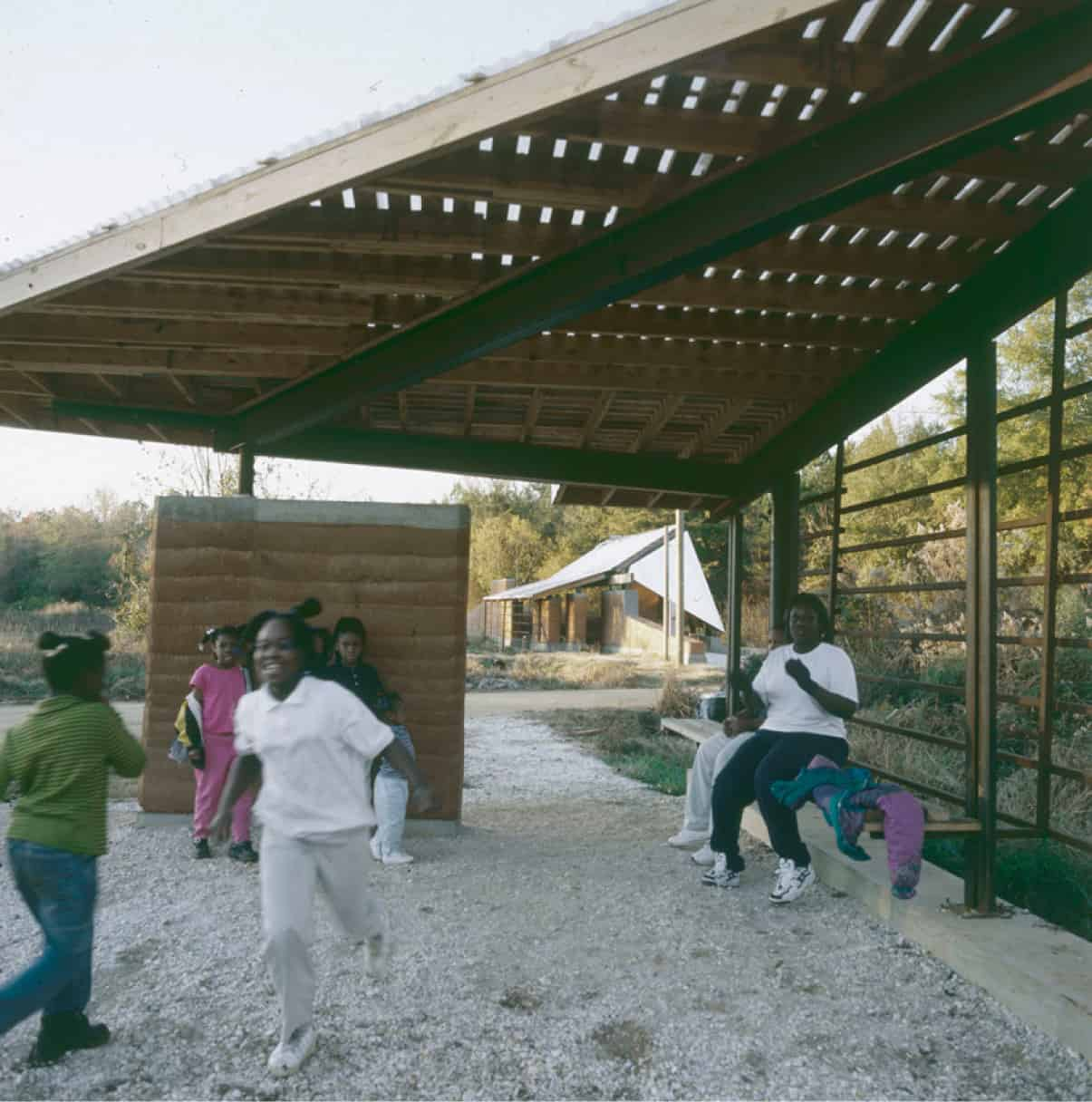 Children playing under the basketball court's roofed area