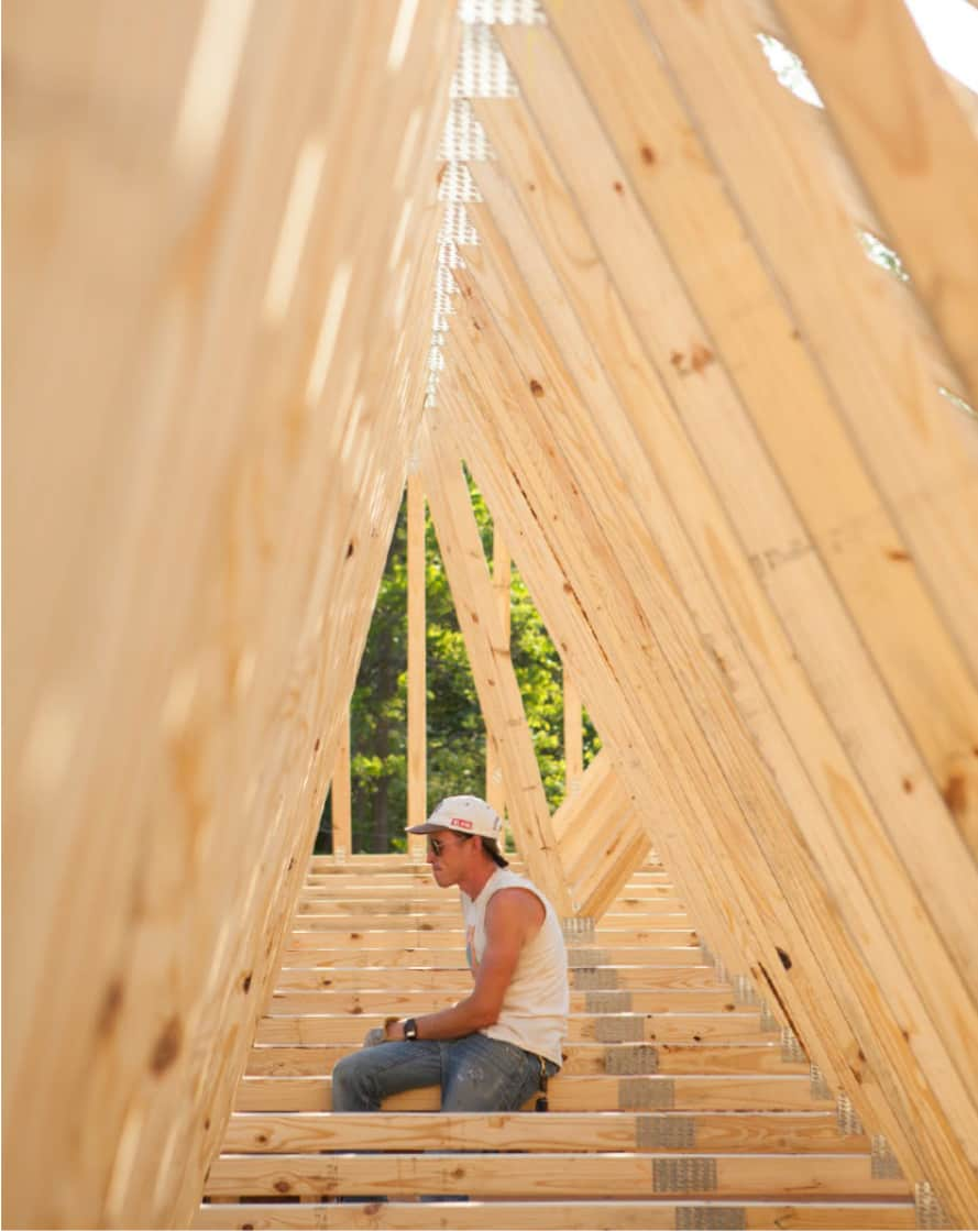 student sitting in house framing