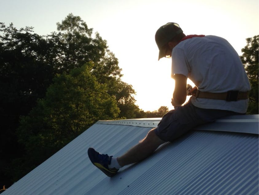Student uses drill on roof of Michele's House