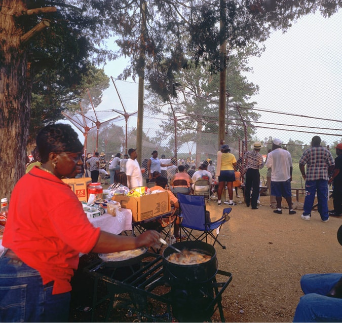 A woman cooks food as fans watch the baseball game