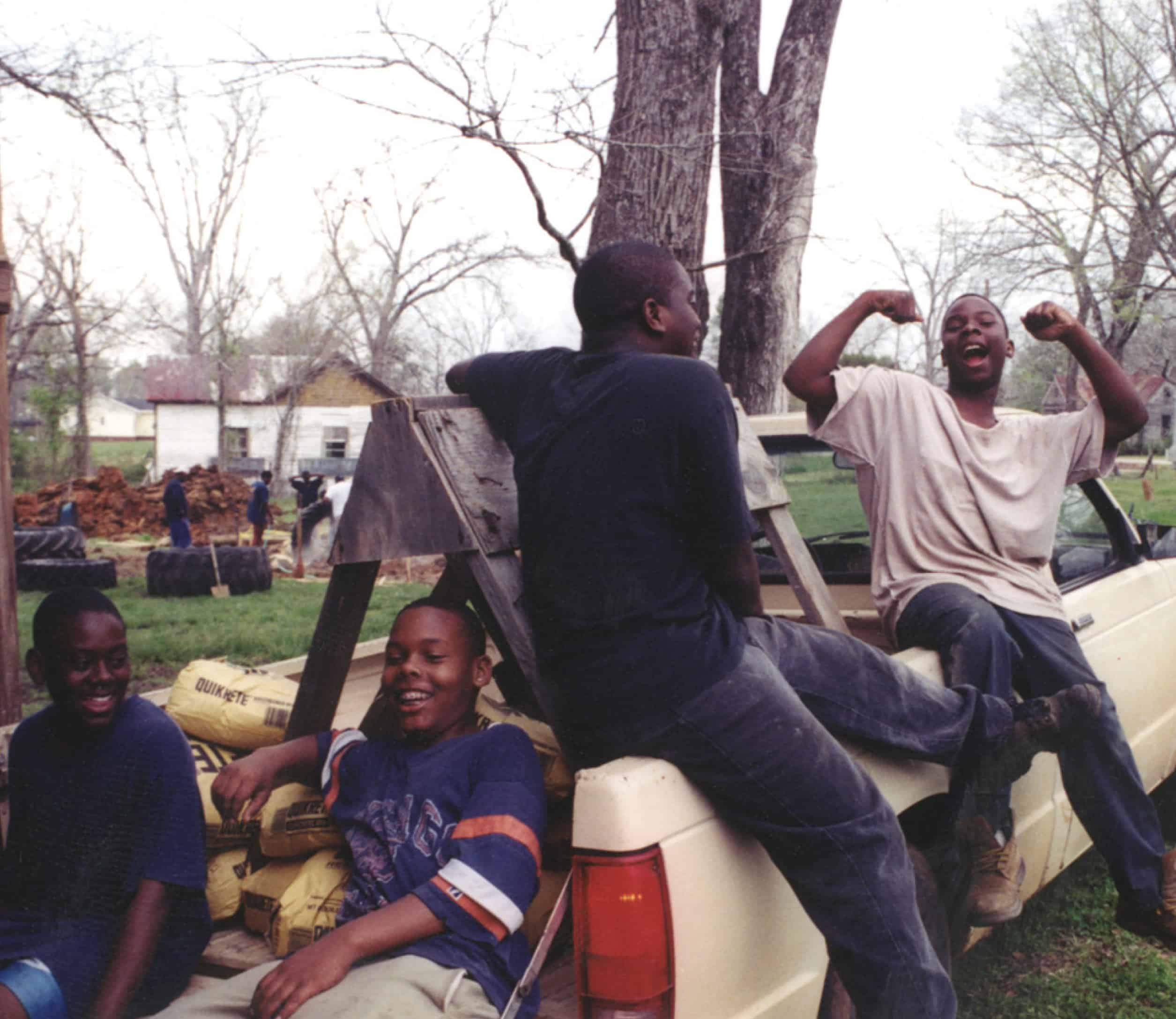 kids sit in the back of pickup truck and pose for the camera
