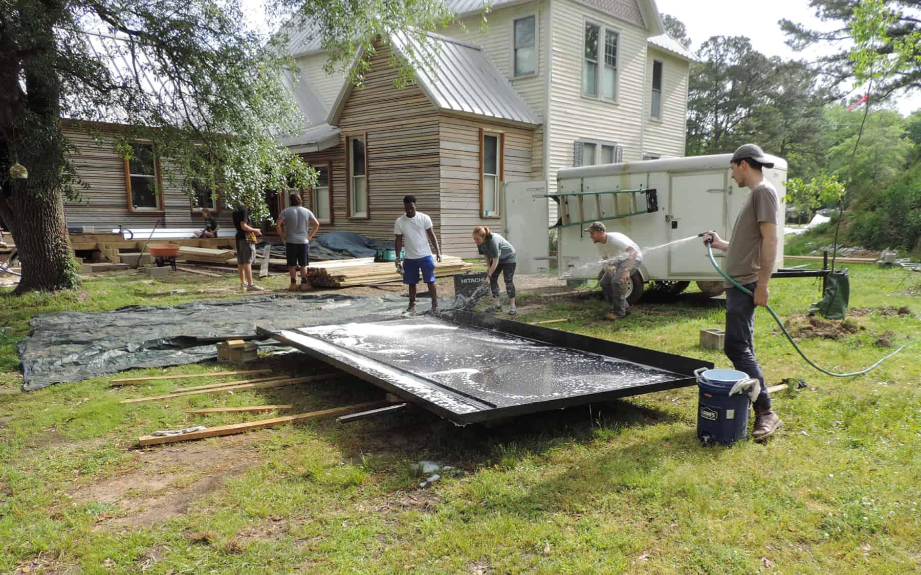 Students washing rainwater collection panel