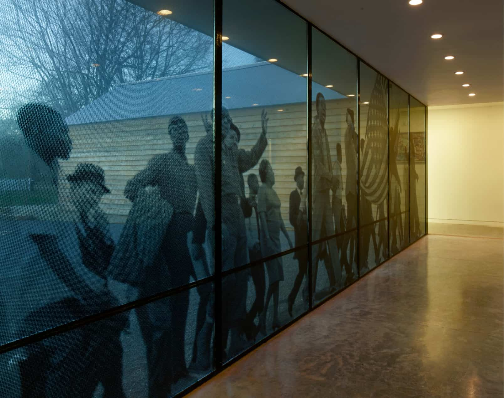view of hallway connecting homes that shows civil rights marchers on glass