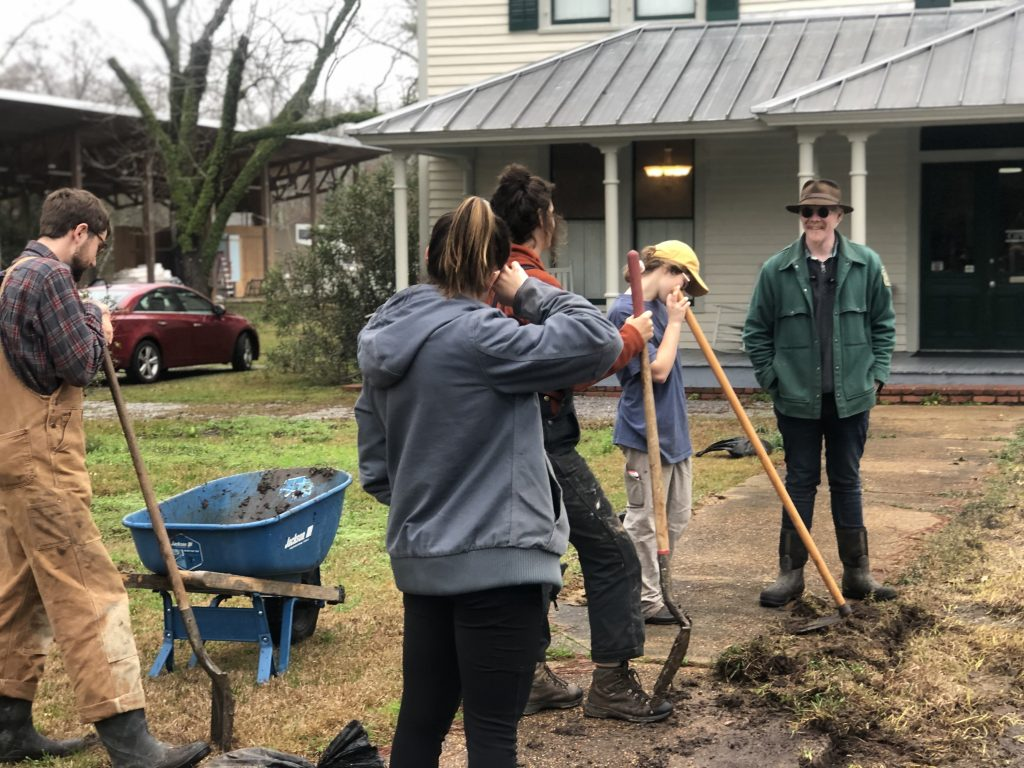 Students clear grass from front walk