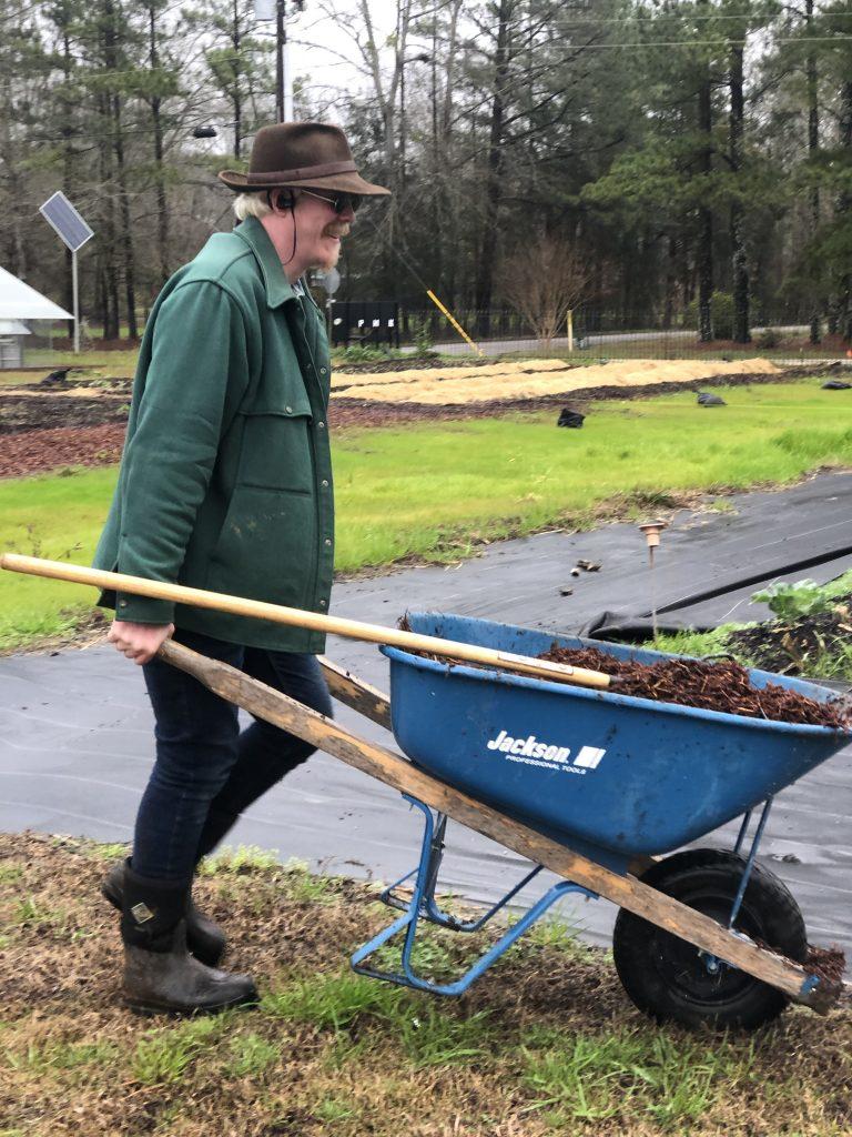 Farm manager Eric pushes a wheelbarrow of mulch