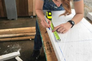 student measuring and marking foam