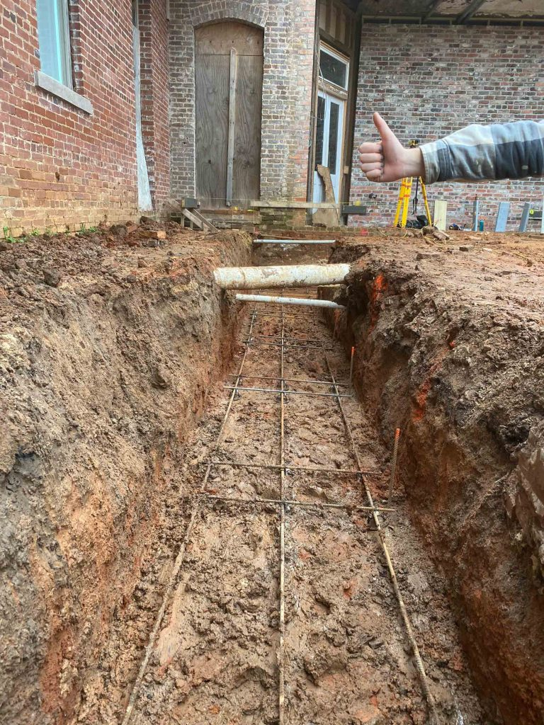 Thumbs up, rebar in all tied together in the trench
