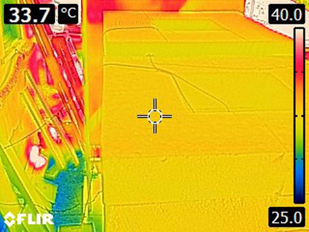 Thermal camera image of the top of concrete chimney after radiant barrier installed. Temperature registering at 33.7 °C.