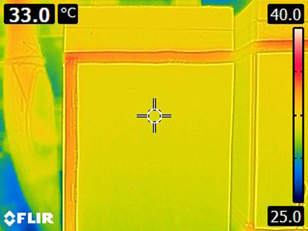 Thermal camera image of the side of concrete chimney after radiant barrier installed. Temperature registering at 33.0 °C.