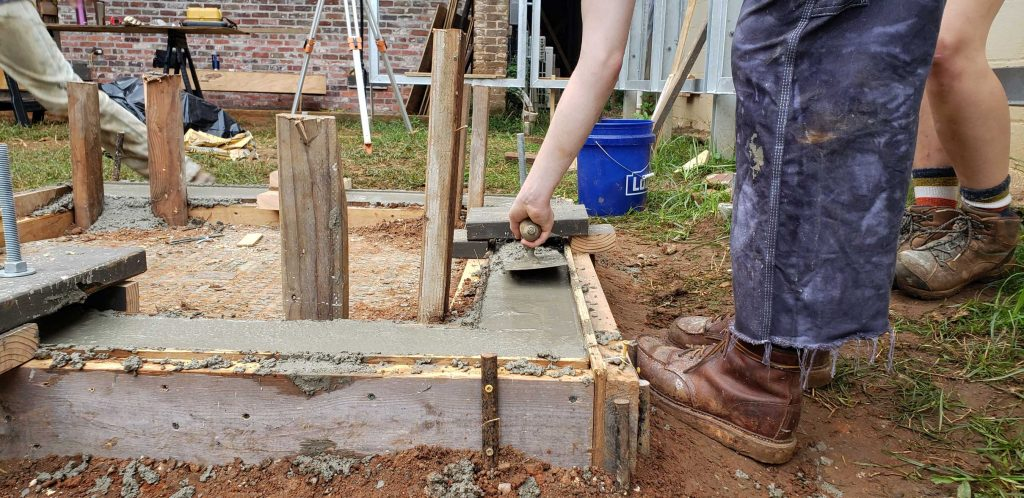 Student screeding the surface of concrete