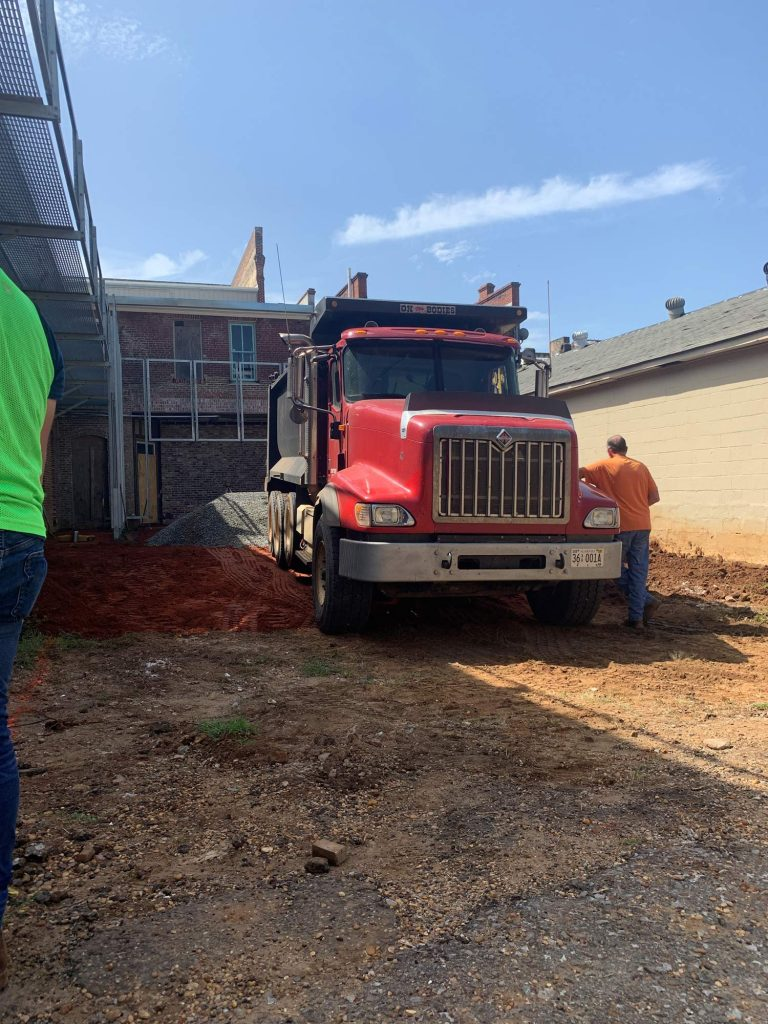 Truck drops off gravel at site