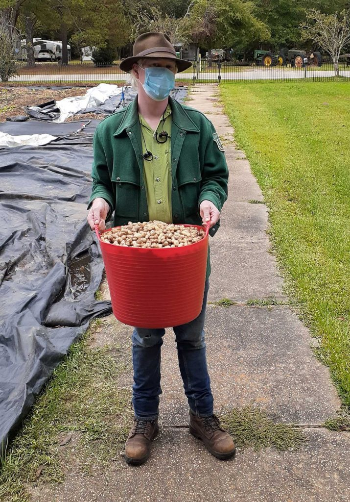 Eric holds a ten-gallon tub of dried peanuts en route to the kitchen