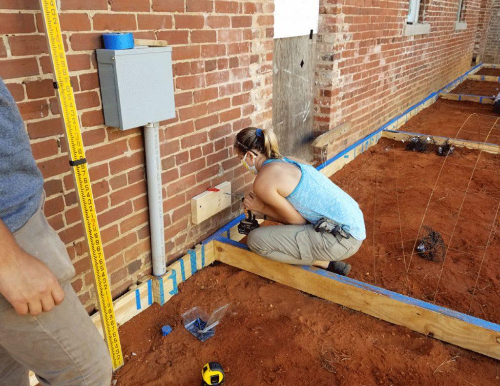 student drills batter board into brick wall