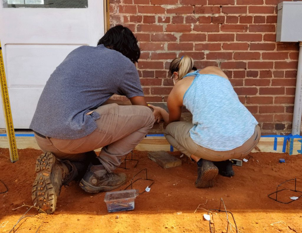 two students drill batter board to brick wall