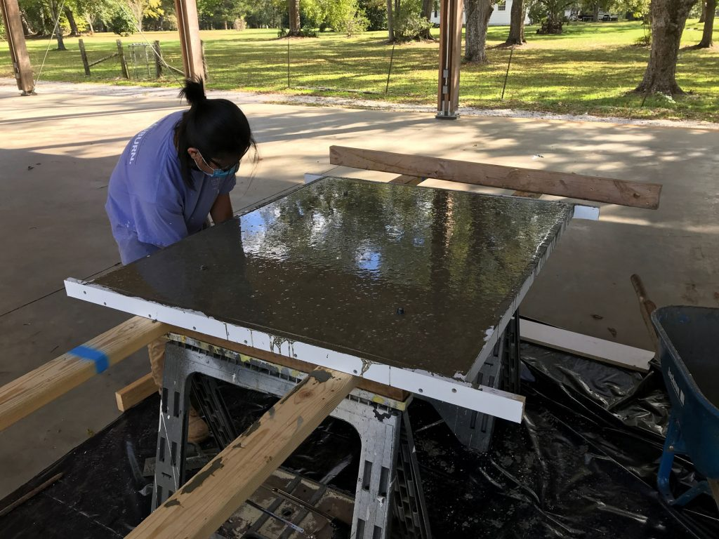 student hits bottom of panel mold to rid concrete of air bubble