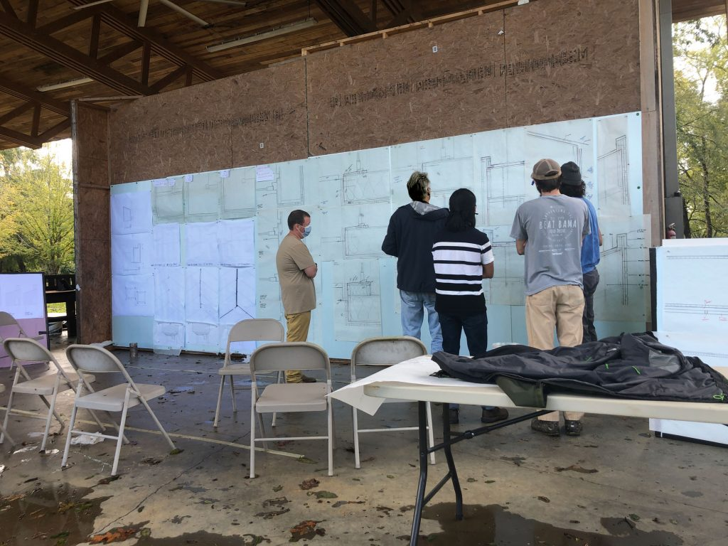 students and professors gather in front of a wall full of detail drawings
