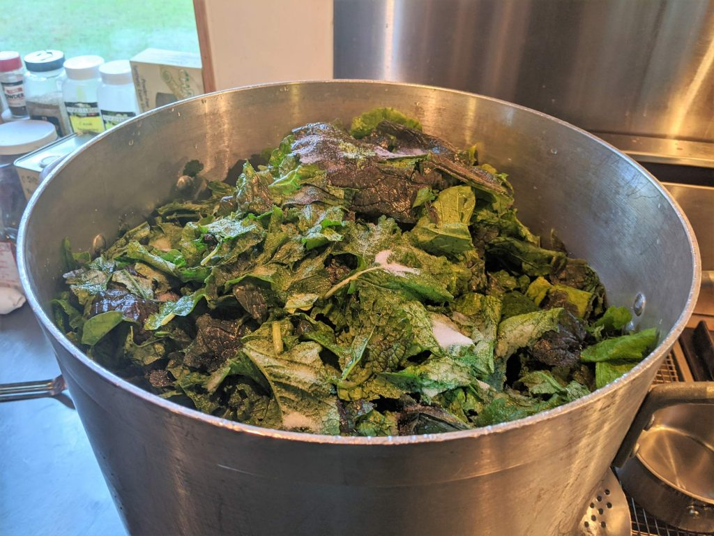 A big pot of mustard greens cooking in the kitchen