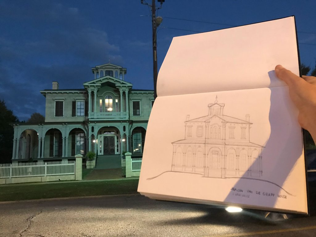 A student holds their drawing of Jemison Mansion in front of the home