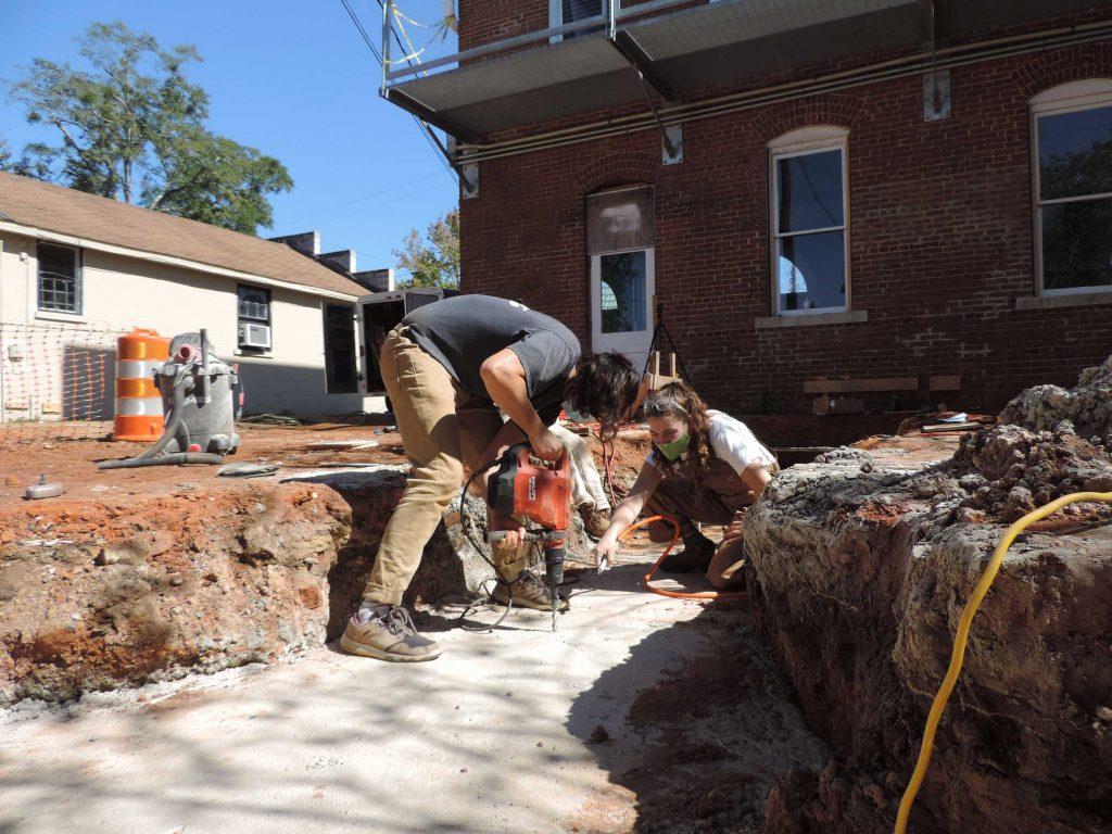 Student drilling into concrete