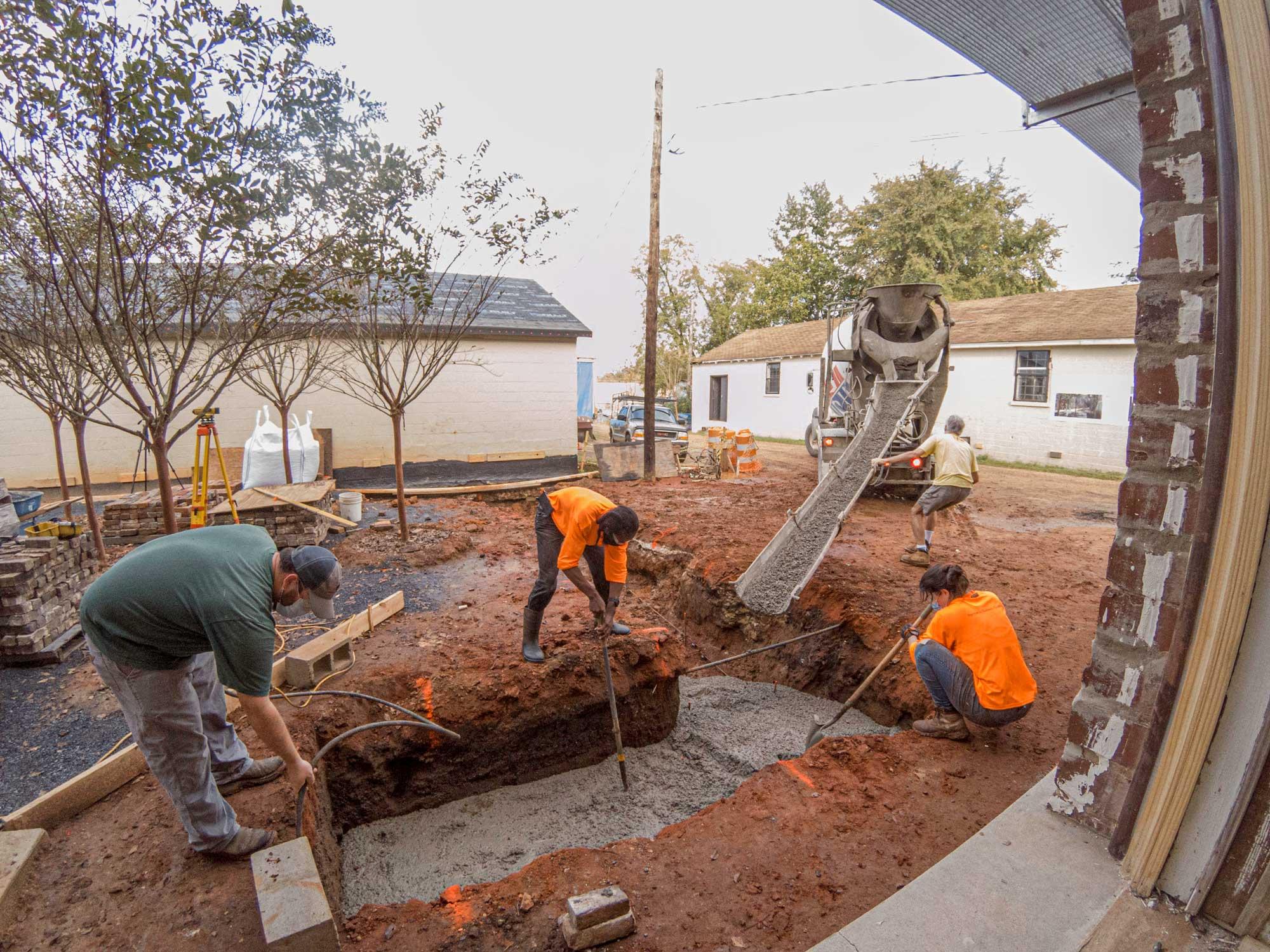 students pouring concrete