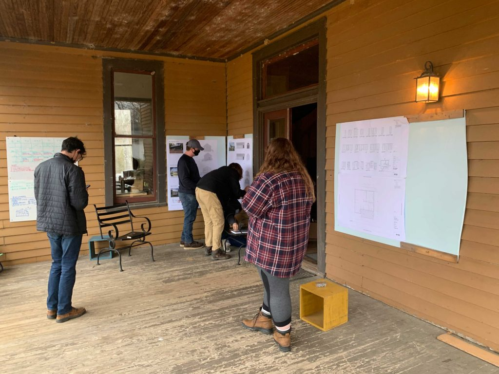 Group of students presents findings during pin-up on the porch of Spencer house.
