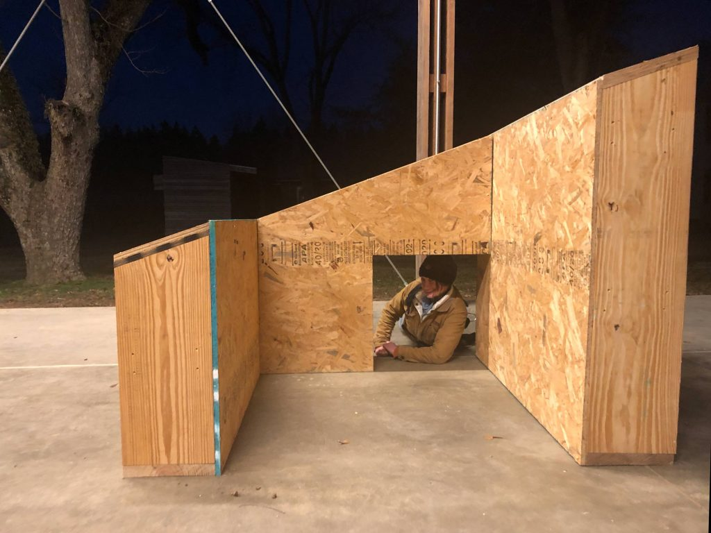 Student looks through small door opening in mock-up stud wall