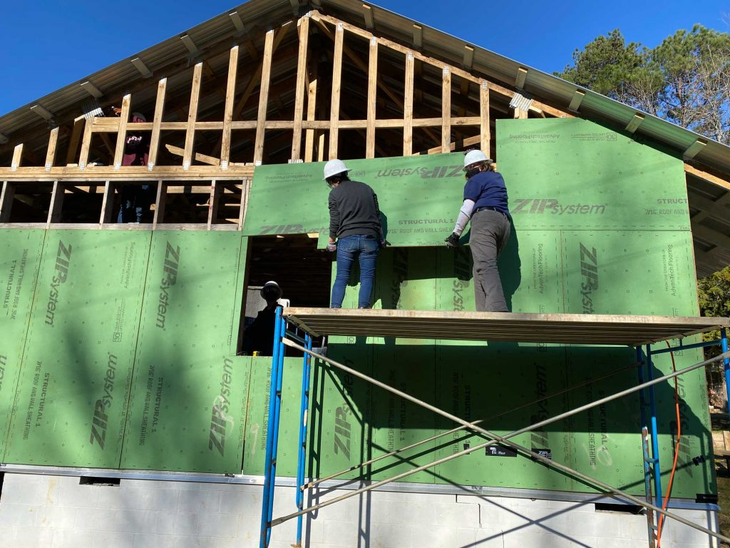Two students attaching sheathing onto exterior