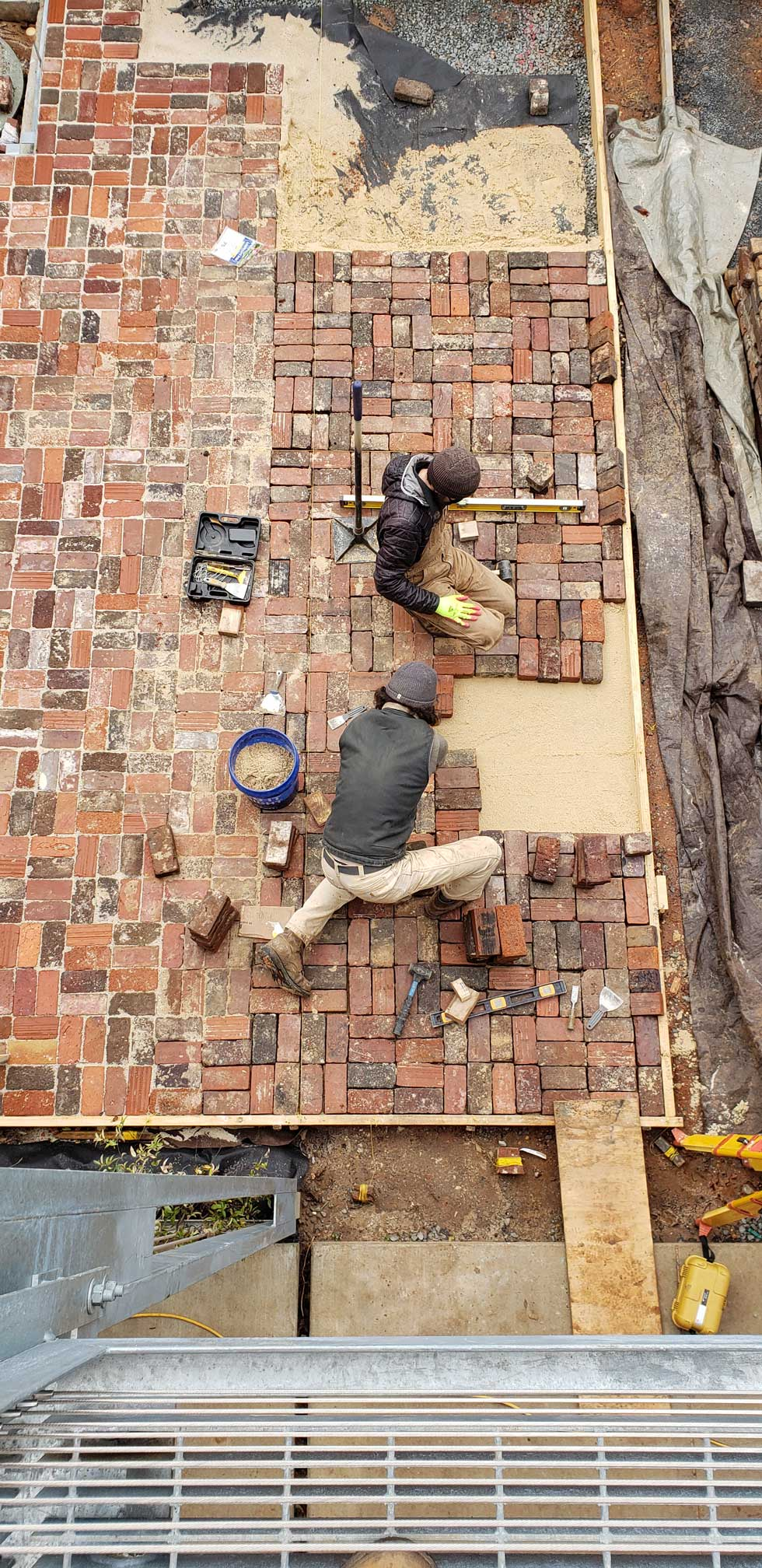 Students laying bricks on sad