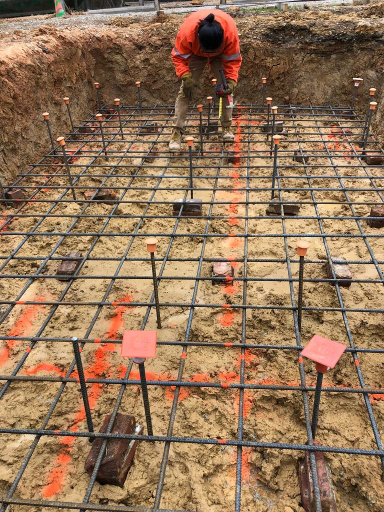 student places rebar caps on vertical rebar pieces