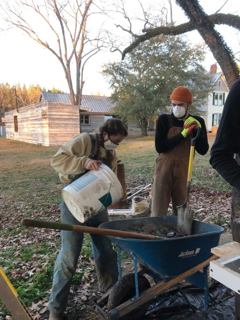 student adds water to concrete mix in wheel barrow