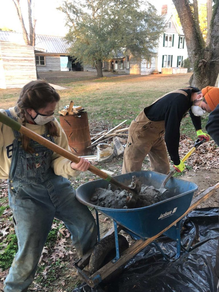 students mixing concrete in wheel barrow with shovels