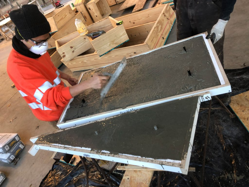 student trowels concrete in formwork