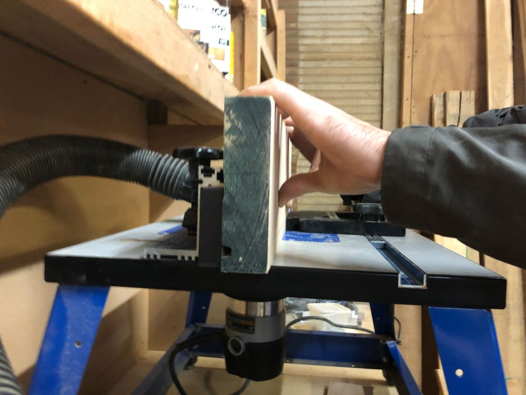students routes groove into wood using router table