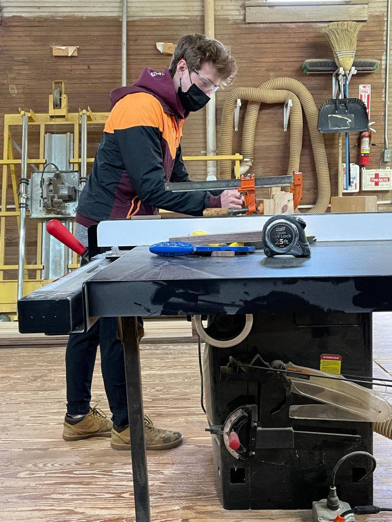 student uses the table saw in wood shop