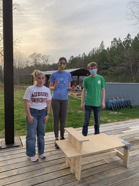 three students stand behind their handmade bench